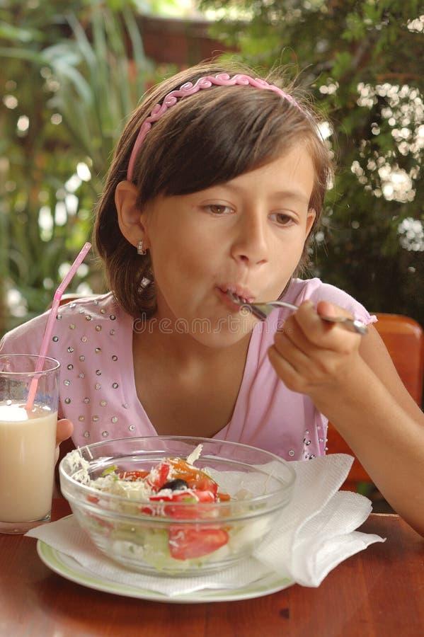 Girl eating salad stock photo