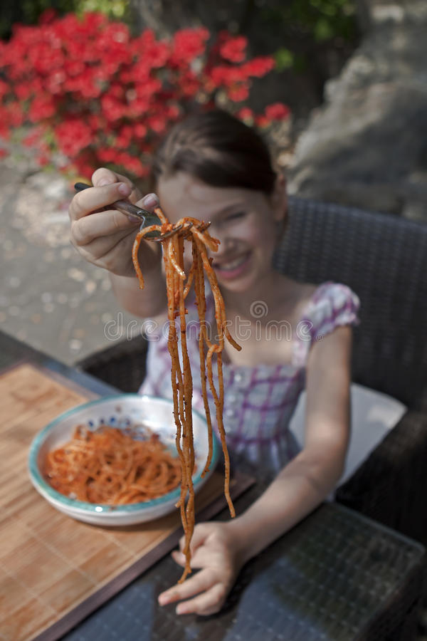 Girl is eating spaghetti royalty free stock photo