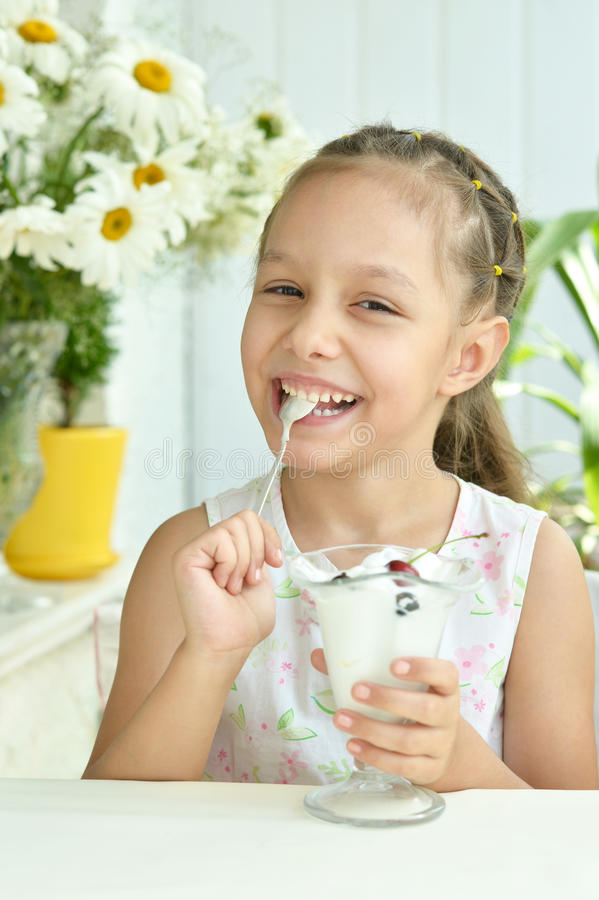 Girl eating sweet dessert with berries. Portrait of little girl eating sweet dessert with berries stock images
