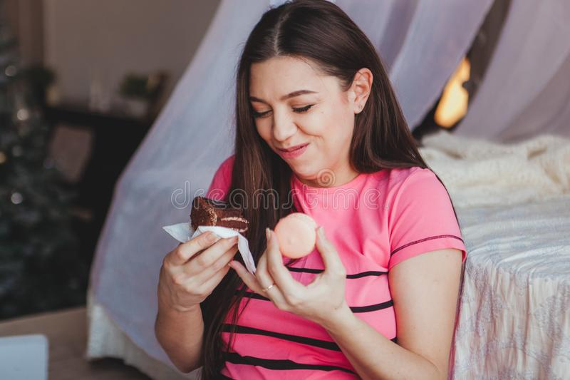 Girl eating tasty browny cake with in bedroom. Sweet dessert. Good morning.  stock photography