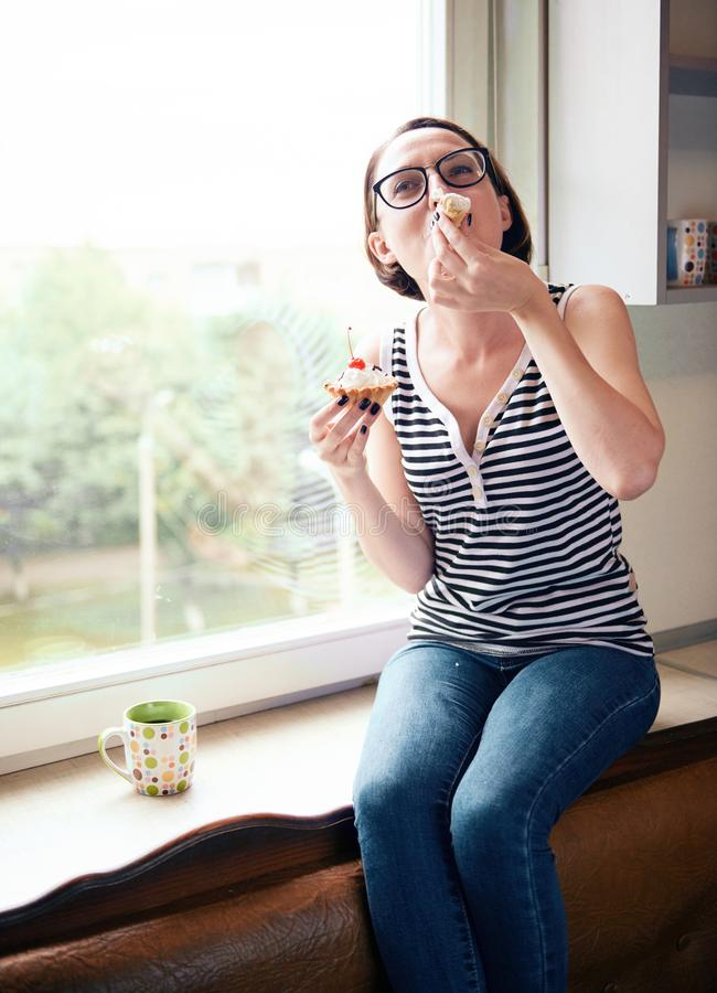 Girl eating tasty cakes, sitting by the window, sweet food and pleasure royalty free stock photos