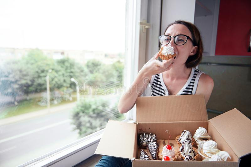 Girl eating tasty cakes, sitting by the window, sweet food and pleasure stock images
