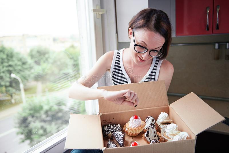 Girl eating tasty cakes, sitting by the window, sweet food and pleasure royalty free stock photo