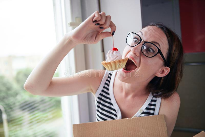 Girl eating tasty cakes, sitting by the window, sweet food and pleasure stock photos