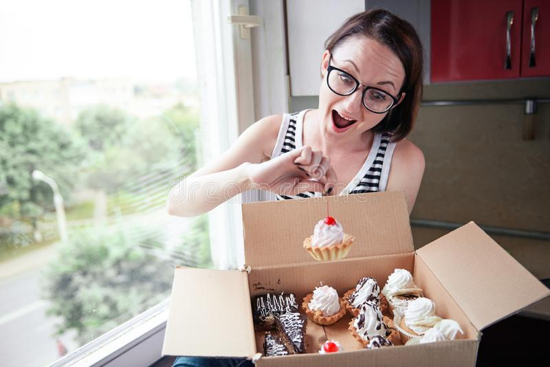 Girl eating tasty cakes, sitting by the window, sweet food and pleasure stock photography