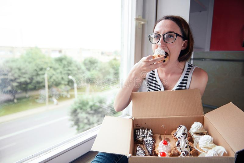 Girl eating tasty cakes, sitting by the window, sweet food and pleasure stock photo