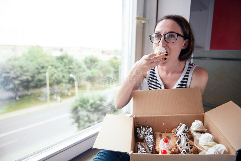 Girl eating tasty cakes, sitting by the window, sweet food and pleasure royalty free stock photography