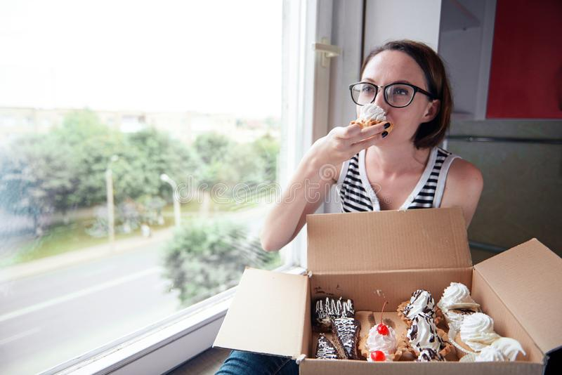 Girl eating tasty cakes, sitting by the window, sweet food and pleasure royalty free stock images
