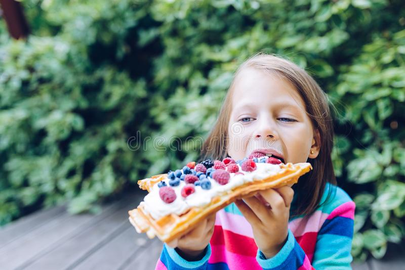Girl eating a waffle with whipped cream, raspberries and blueberries in the garden. Waffles - girl eating a waffle with whipped cream, raspberries and royalty free stock images