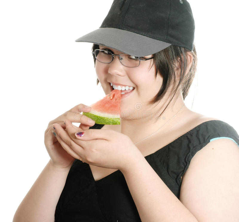Girl Eating Watermelon. A young girl wearing a baseball cap is eating a slice of watermelon, isolated against a white background stock images