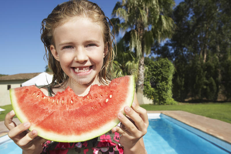 Girl Eating Watermelon Against Pool stock images