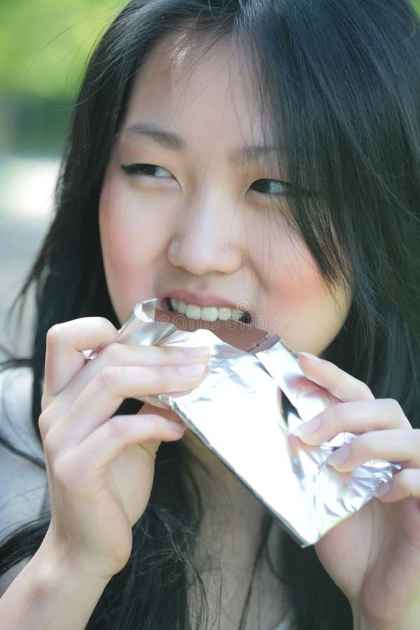 Girl eats chocolate stock photography
