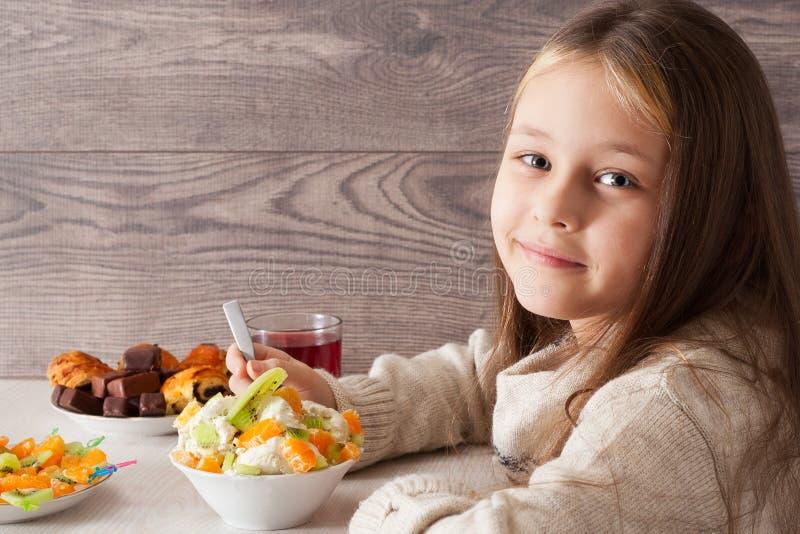 Girl Eats Fruit Dessert In Cafe Stock Photo