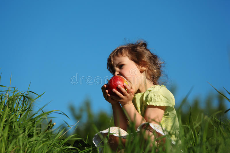 Girl eats red apple in grass against blue sky stock image