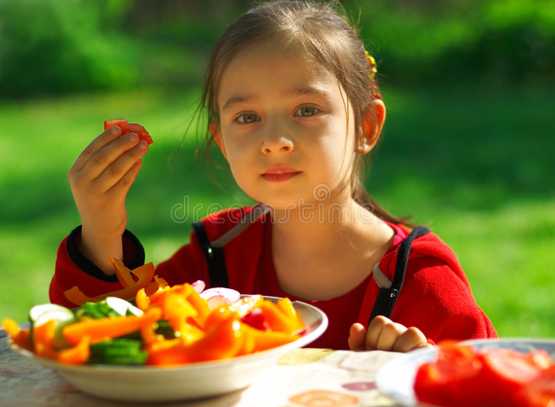 Girl eats vegetables stock photography