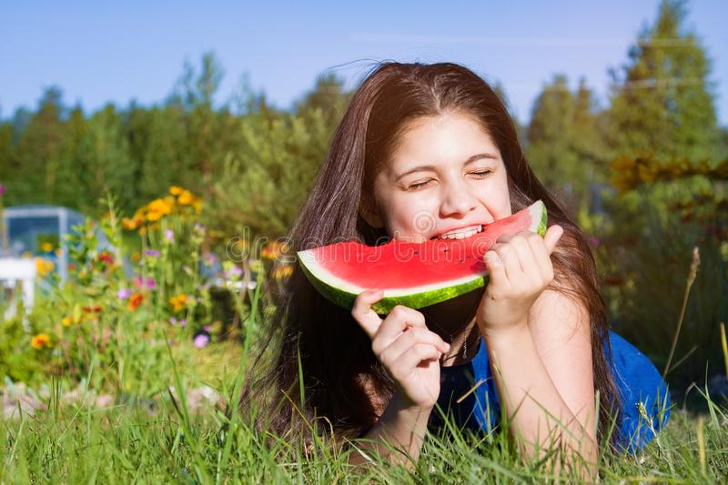 Girl eats watermelon outdoors in summer park, healthy food stock photography