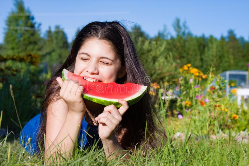 Girl eats watermelon outdoors in summer park, healthy food stock photos