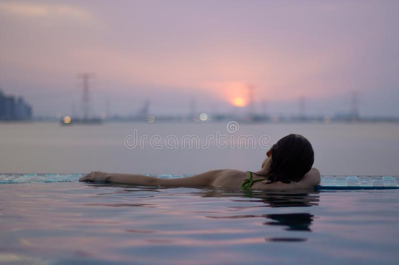 Girl at the edge of infinity pool stock photos