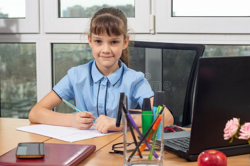 A girl of eight years old at the table in the office plays in the office employee royalty free stock photo