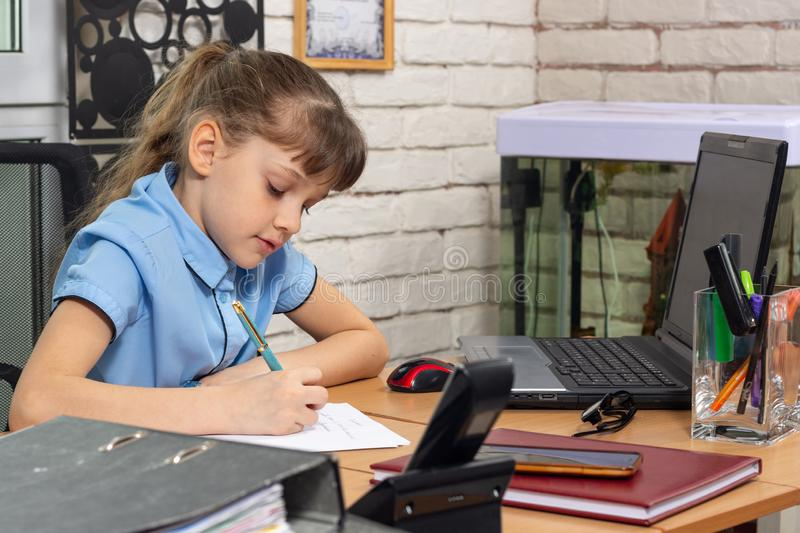 A girl of eight years old works at a table in an office stock photos