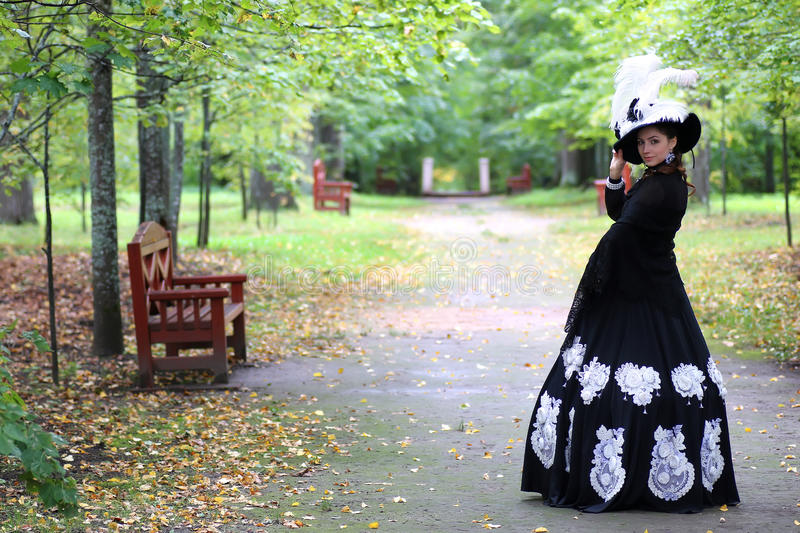 Girl eighteenth century dress in park. Beautiful girl in Victorian dress in the manor summer day stock photos