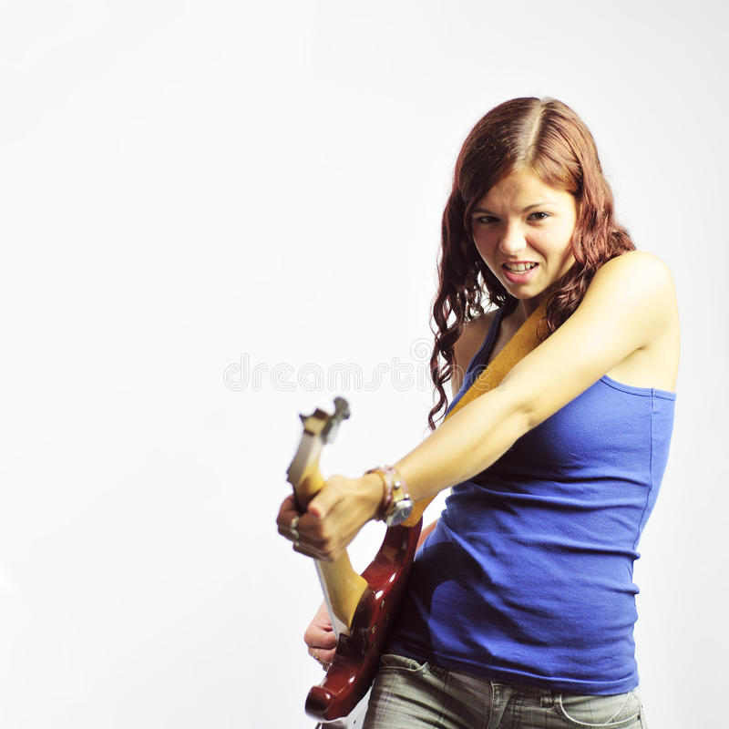 Girl with Electric Guitar. Teenage girl playing a electric guitar with an aggressive pose. Square image with a neutral background with plenty of copy space royalty free stock photography