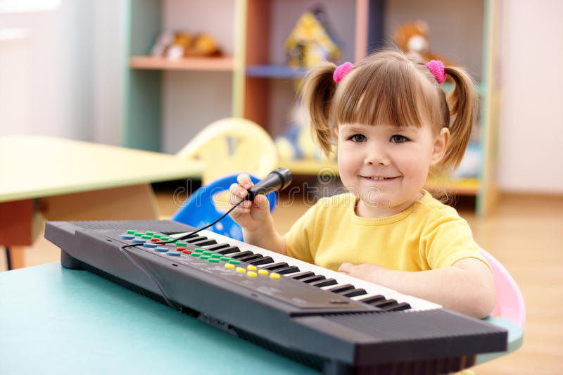 Girl with electronic piano and microphone royalty free stock image