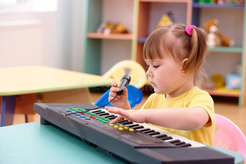 Girl with electronic piano and microphone. Little girl with electronic piano and microphone in preschool royalty free stock photo