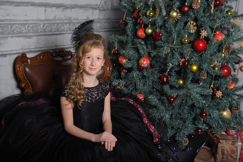 Girl in elegant black dress with a feather in the evening hairstyle by the Christmas tree royalty free stock image