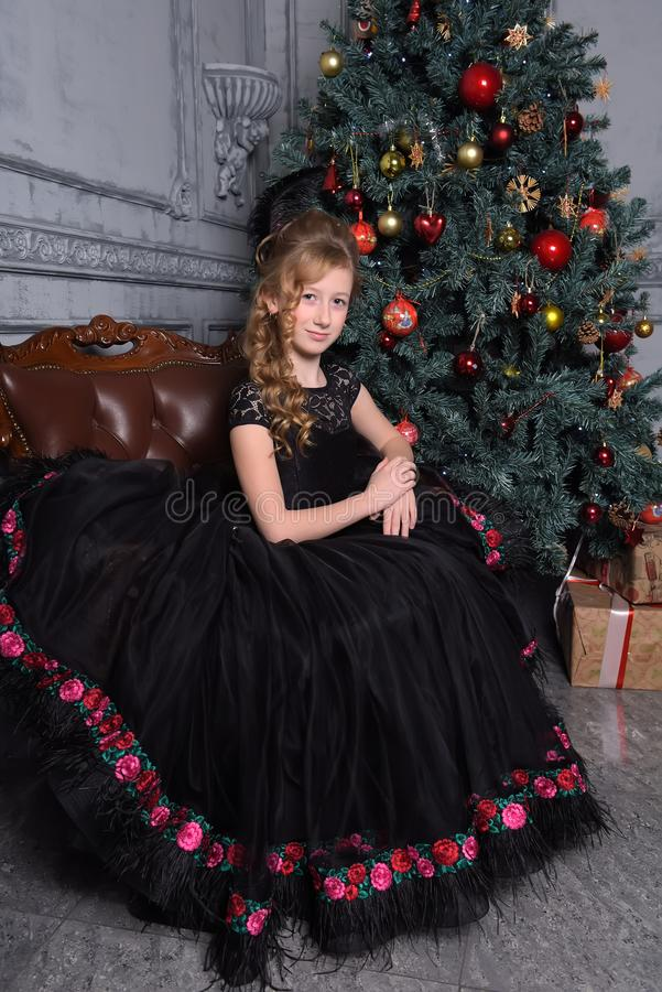 Girl in elegant black dress with a feather in the evening hairstyle by the Christmas tree stock images