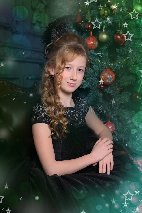 Girl in elegant black dress with a feather in the evening hairstyle by the Christmas tree royalty free stock images