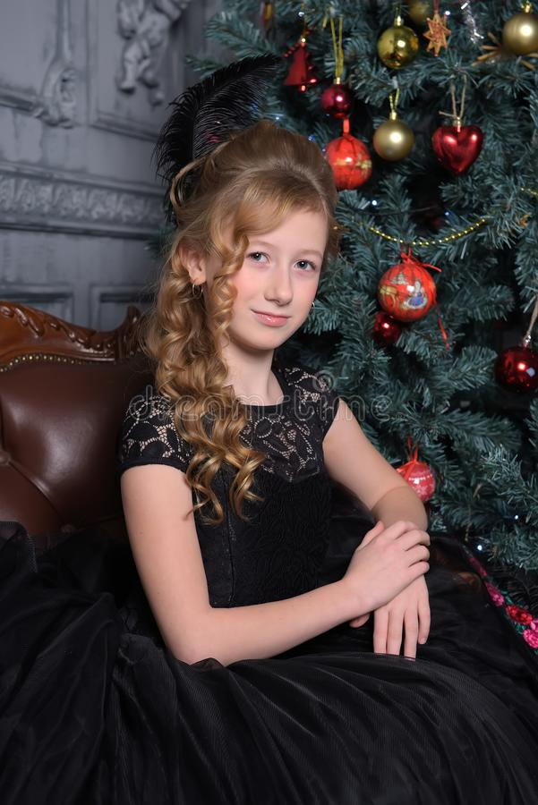Girl in elegant black dress with a feather in the evening hairstyle by the Christmas tree royalty free stock photos