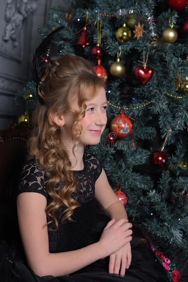 Girl in elegant black dress with a feather in the evening hairstyle by the Christmas tree stock image