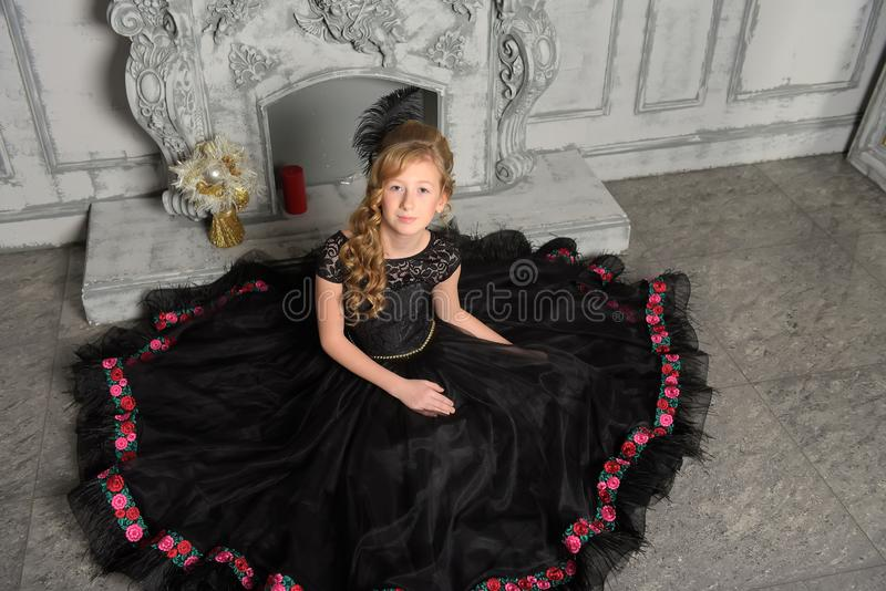 Girl in elegant black dress is sitting in the gray stock photography