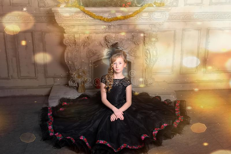 Girl in elegant black dress is sitting in the gray royalty free stock image