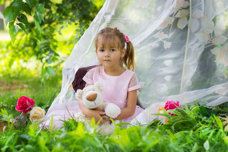 The girl in an elegant dress sits with a teddy bear in a tent outdoors stock photo