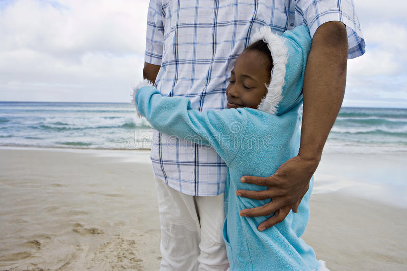 Girl (7-9) embracing father on sandy beach, girl wearing blue fleece with hood, smiling, eyes closed royalty free stock images