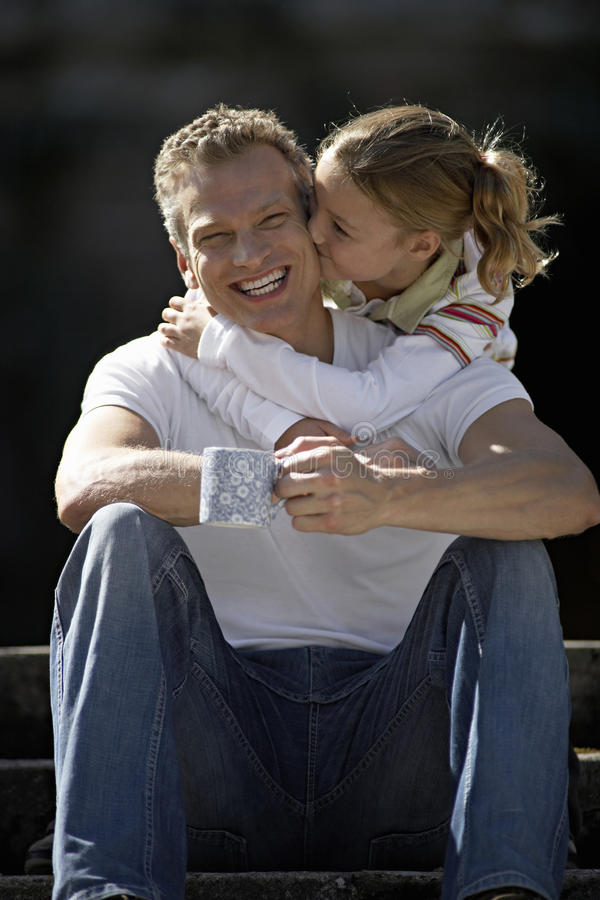 Girl (9-11) embracing father sitting on steps, kissing man on cheek, smiling, front view. Girl (9-11) embracing father sitting on steps, kissing men on cheek royalty free stock photos