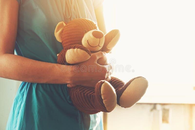 Girl embracing vintage teddy bear stock image