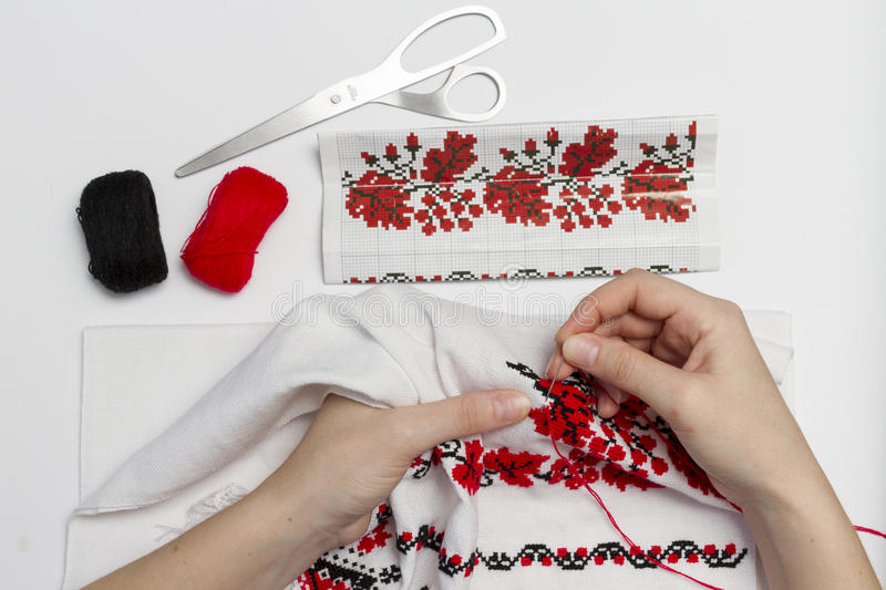 Girl embroider pattern on a towel close-up. Woman embroiders national pattern red thread on a towel stock image
