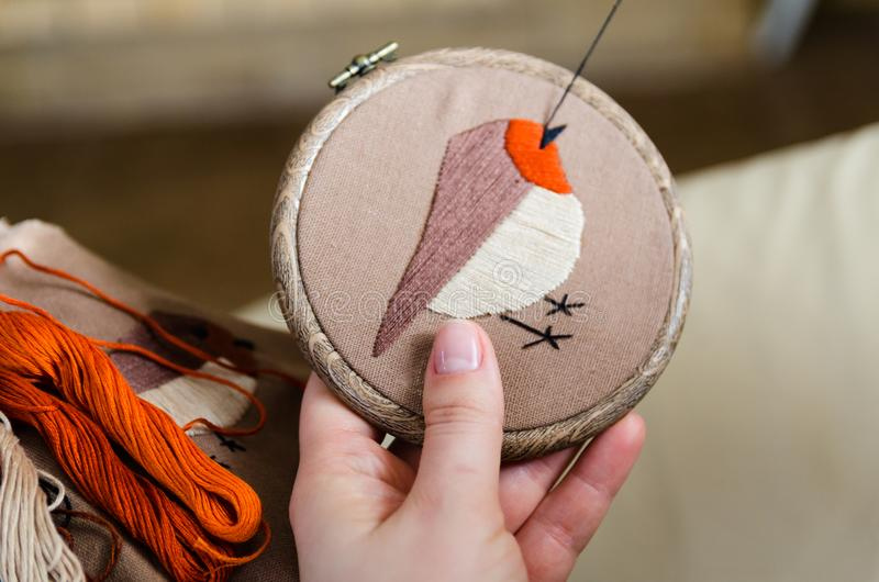 Girl embroiders a bird with a stitch. DIY concept, Hobbies, creativity, clothing and interior decoration stock photo