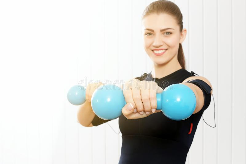 The girl is engaged with blue dumbbells. royalty free stock photography
