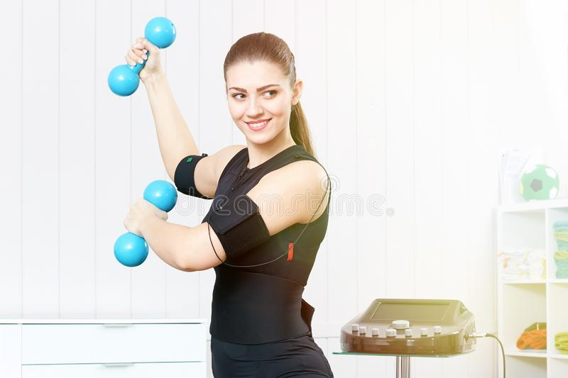 The girl is engaged with blue dumbbells. stock photography