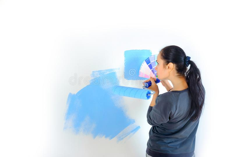 The girl is engaged in a choice of paints for the walls of the room. Room design, the girl is engaged in a choice of paints for the walls of the room, isolated royalty free stock photography