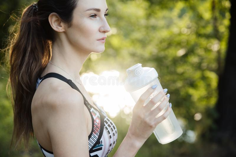 The girl is engaged in fitness and meditates in the park city stock image
