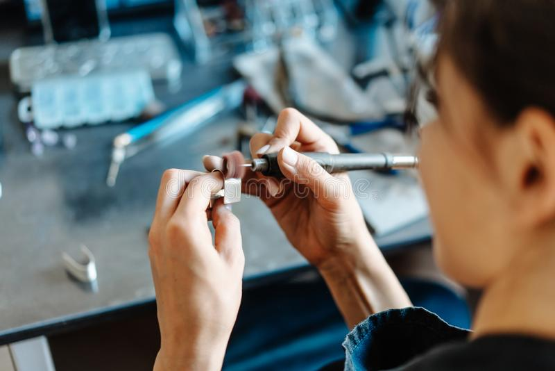 The girl is engaged in jewelry business. The girl works on a jewelry in the workshop stock photos