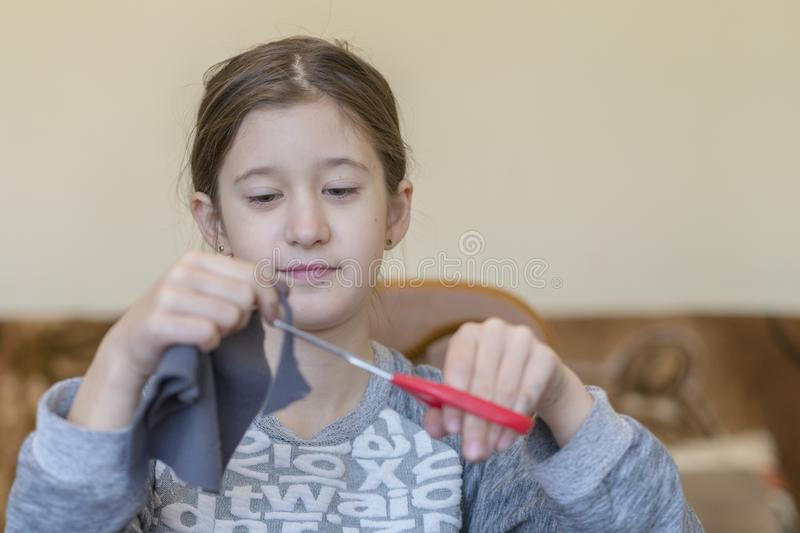 Girl engaged in needlework. Little girl with scissors stock photos