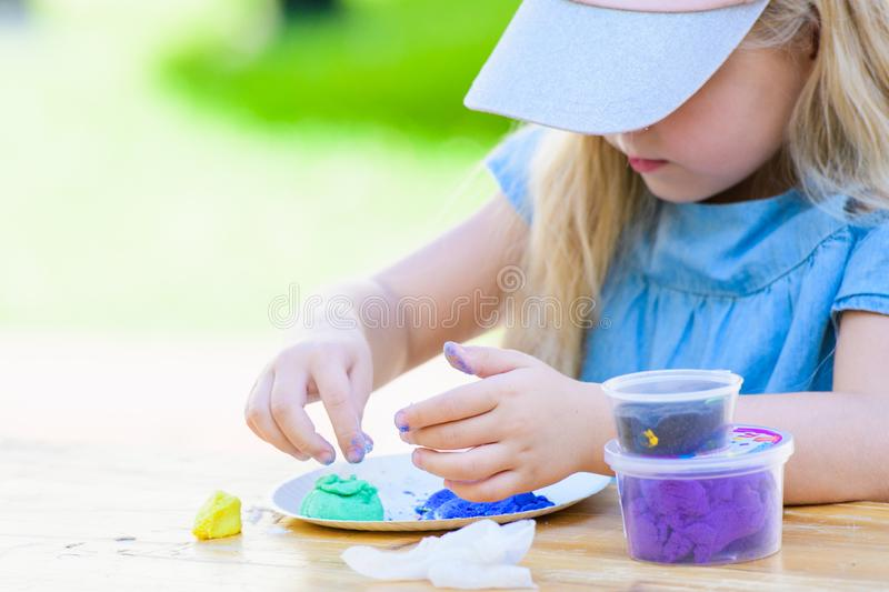 Girl is engaged in needlework at the table. games on the street. educational games.  stock photography