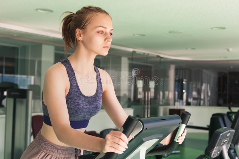 Girl is engaged on a stationary bike. Young blond sporty girl is engaged on a stationary bike in a gym stock photo
