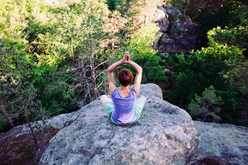 Yoga on fresh air. Girl engages in yoga on the top of mountain, solitude with nature and meditation on grief. healthy way of life royalty free stock photos